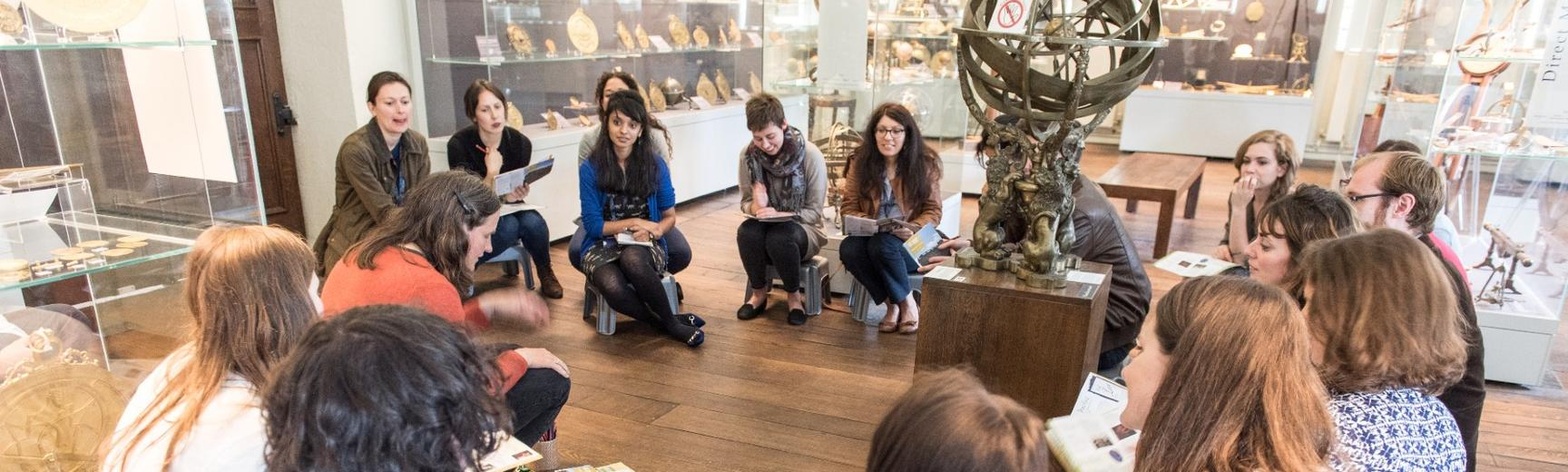 A group of people in a museum hold exhibition guides and sit in a circle discussing