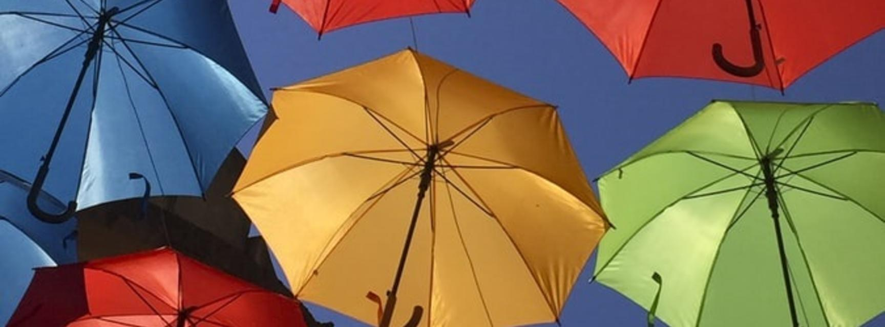 Image of yellow, orange, green, blue, pink, and purple umbrellas in the air against the blue sky background