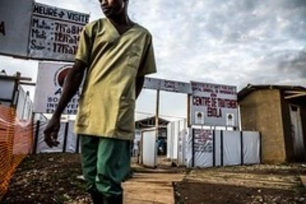 Person standing in front of a centre for ebola treatment with white plastic signs