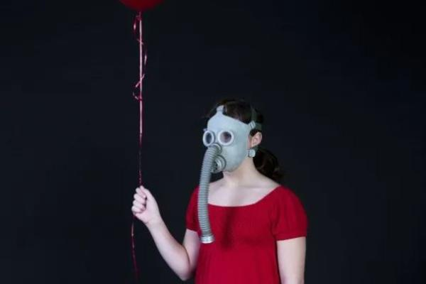 Woman in red dress and wartime gas mask holds helium red ballon