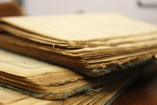yellowed and rough edges of an old book, stacked on top of each other