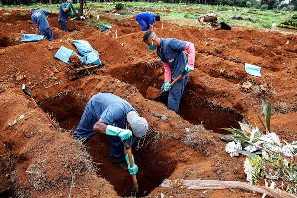 Gravediggers in Brazil's Vila Formosa cemetery in Sao Paulo, exhume old graves to make way for more victims of COVID-19. Sebastiao Moreira/EPA