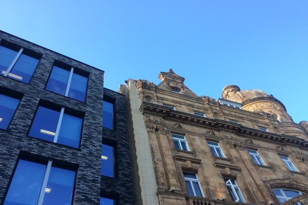 Image of two adjacent facades; carved sandstone with columns and French windows on the right, sleek black brick and blue glass on the left