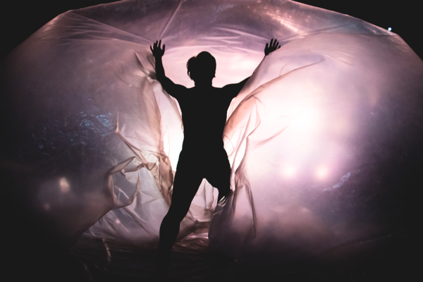 Backlit dancer heading into large transparent bubble
