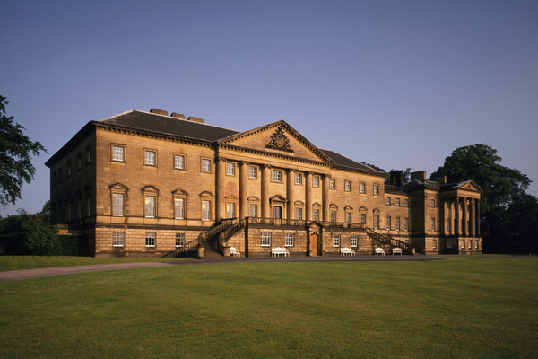 Exterior shot of Nostell Priory. A large building of warm-coloured stone, imitating Classical architecture with columns and pediment, and 21 sets of triple windows. The foreground of the image is a green lawn.