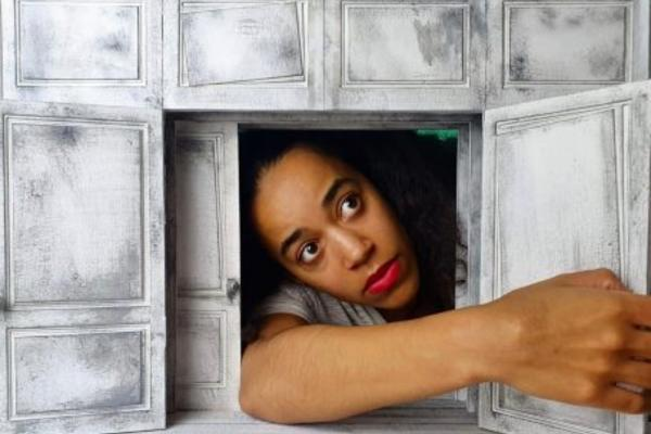 Actress playing Alice in Wonderland reaches through a small door