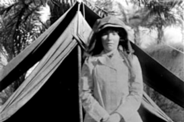 black and white photograph (1909) of woman standing in front of a tent, palm trees behind her