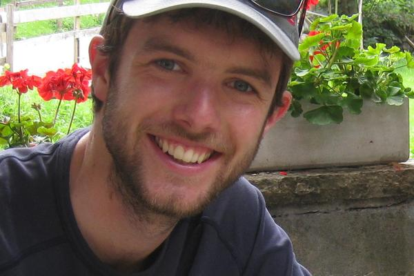 Image of Tim Middleton smiling, wearing a hat with small boxed red flowers behind him