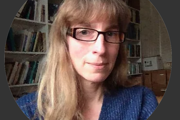A picture of Katja. She is wearing a blue long sleeved top, has long brown hair with a fringe and square dark glasses