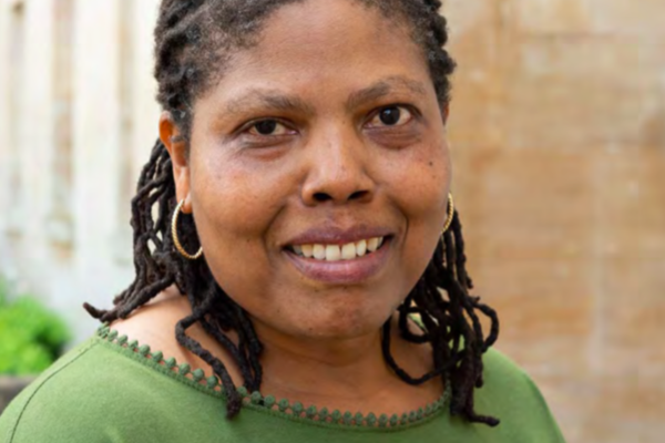 Professor Audrey Mbogho, wearing a green shirt, smiling at the camera