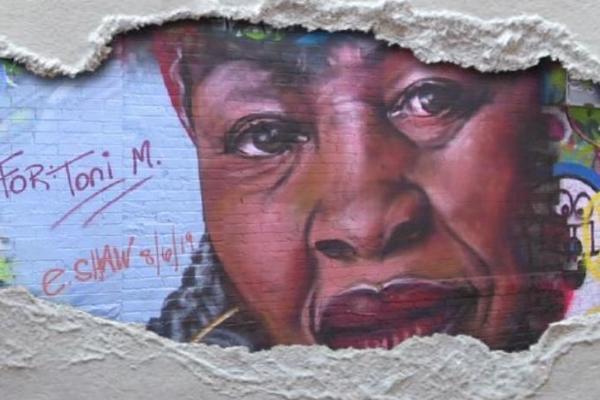 Graffiti art of Toni Morrison showing through ripped paper