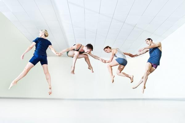 In a dance studio four dancers are in mid-air, holding hands with each dancer in a different pose (straddle, squat, sprint, and stretched legs crossed).
