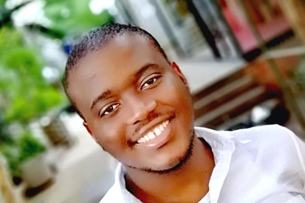 Dr Gcobani Qambela in white shirt smiling at camera