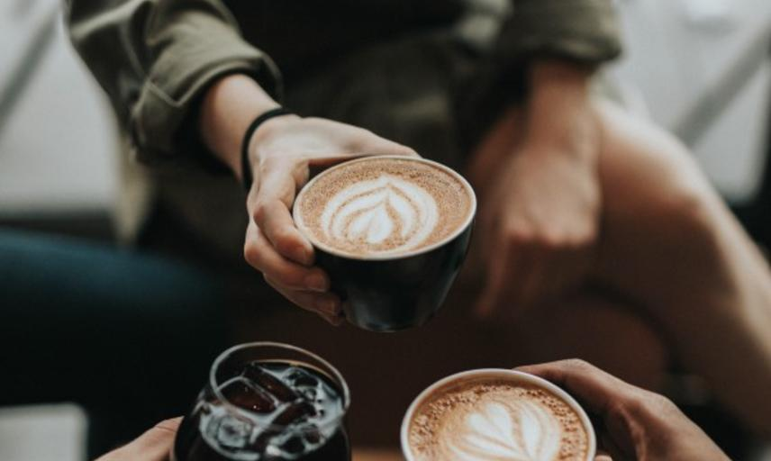 three people holding coffee and cola