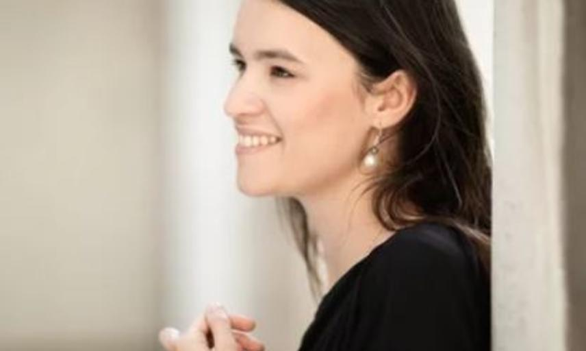 borwn haired, smiling woman dressed in black standing profile against wall, hands softly clasped at chest