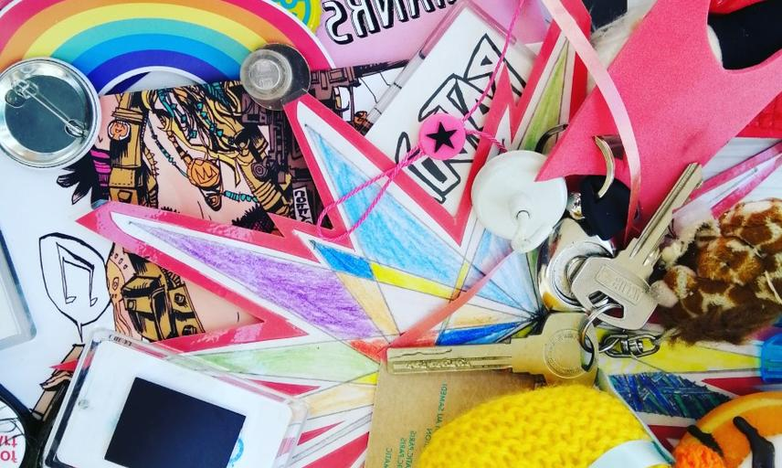 miscellaneous pink and yellow bits and bobs including knitted duck, keys, and paper decorations.