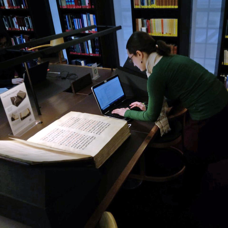 Figure 2. Member of the team studying a very large book. Each page is about 4 times the size of the team-member's laptop, which is a small MacBook.  The book seems more than 15 cm thick.