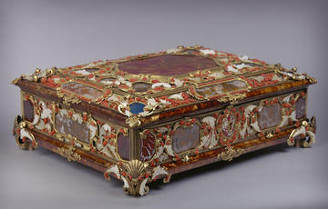 A colourful casket decorated with semi-precious stones, including jasper, agate, lapis lazuli and moss agate. The stones are held in gilt-brass mounts, which are engraved to resemble leaves.