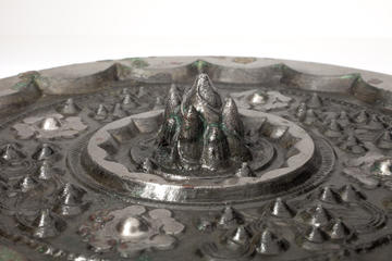 Side view of the mirror's knop in detail. It looks like a mountain while the small bosses look like hills around it.