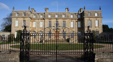 The facade of the mansion behind the locked iron gates