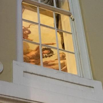 painting of greek scene seen through window panes