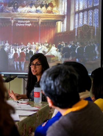 Dr Atwal has long dark hair and wears glasses. She stands in front of a powerpoint presentation depicting a painting of Queen Victoria's wedding. An arrow on the poerpoint points to Maharajah Duleep Singh who is depicted in the audience.