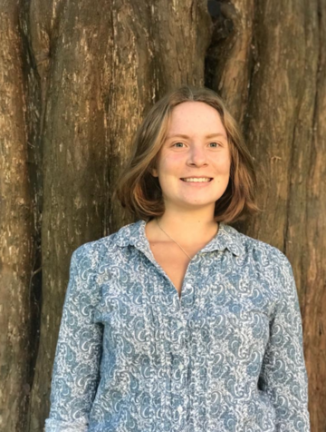 Madeleine has light brown short hair and smiles at the camera. She wears a patterned shirt and stands in front of a massive tree trunk.