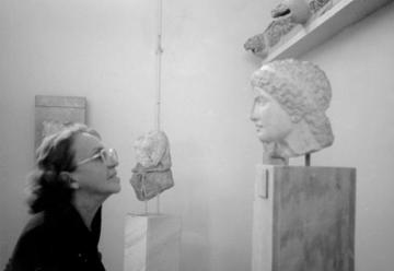 Sophia de Mello Breyner Andresen face to face with the head of a statue in a museum.