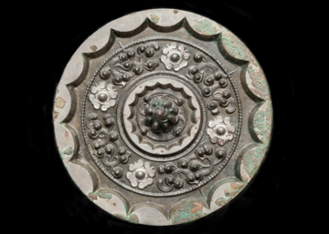 Back view of a bronze mirror decorated with star and cloud pattern. The knob at the centre of the mirror is cast as a mountain, surrounded by four small bosses and an abbreviated cloud design. The thickened rim of the mirror is cast with sixteen arcs.