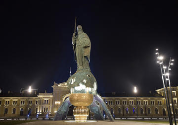 Nighttime image of bronze statue of a man standing on the top of an orb
