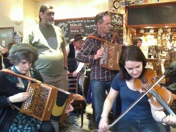 Three musicians at Oxford Folk Festival in a pub in 2013. Two musicians playing the accordeon and KE Fellow Alice Little (at bottom right) playing the violine.