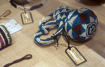 A gourd with two handles made out of blue, white and brown beads in a triangle pattern with a label hung on it lying on a cloth.