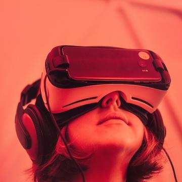Pink tinted photo of a young girl wearing a VR headset and big headphones