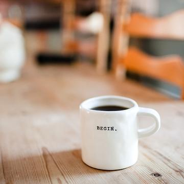 A white mug of coffee sat on a wood table. The mug has 'BEGIN.' printed on it.