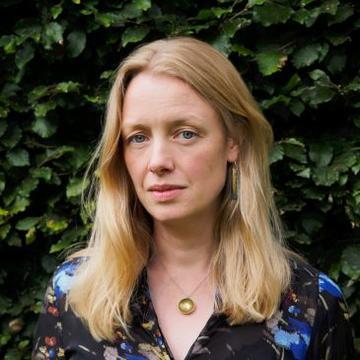 laura tunbridge in floral top, long blonde hair, standing in front of leaves