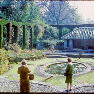 A slightly saturated picture of the Mount Stewart garden with two women admiring the landscape. They have their backs turned to the camera.