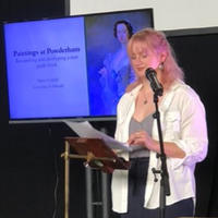 Maisie stands in front of a presentation screen and reads from a script. Maisie is blonde with long hair and wears a white shirt over a grey t-shirt and black trousers.
