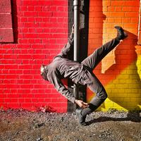 Man in black clothes, bending backwards with his left foot in the air, holding on to a drainpipe attached to a red, orange and yellow wall